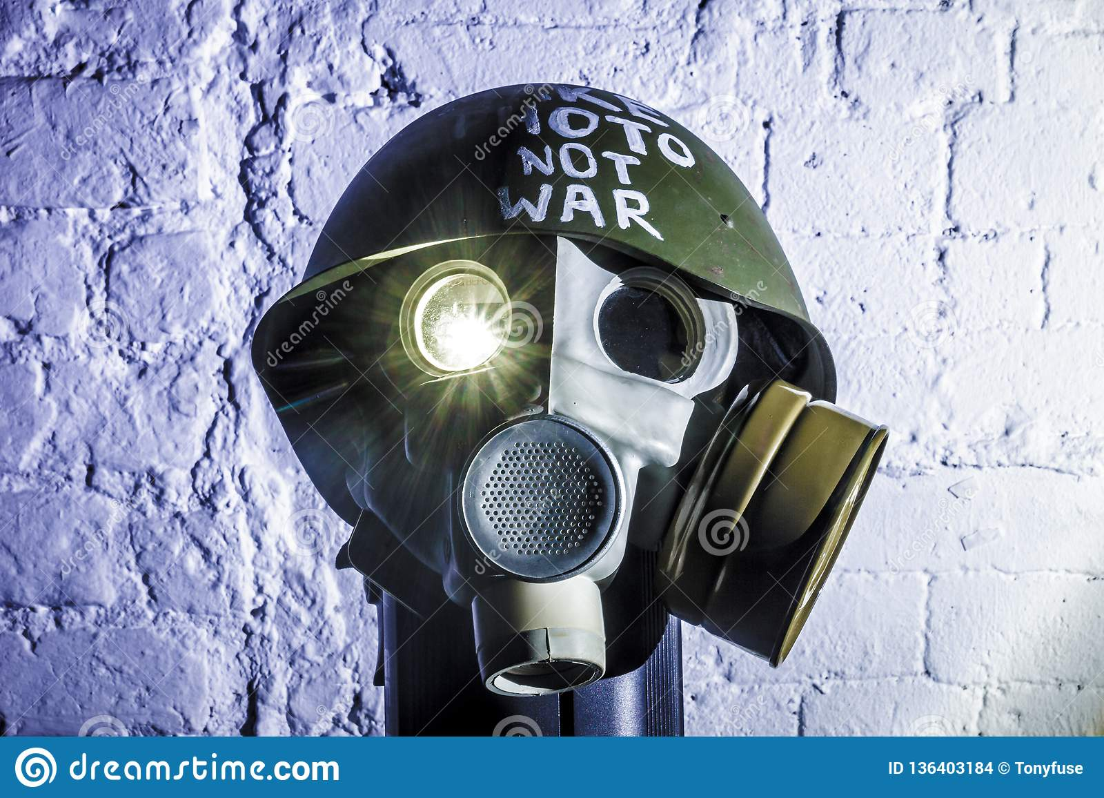 Art picture of a military gas mask on a white brick wall with shadows with flash with the inscription make photo not war on
