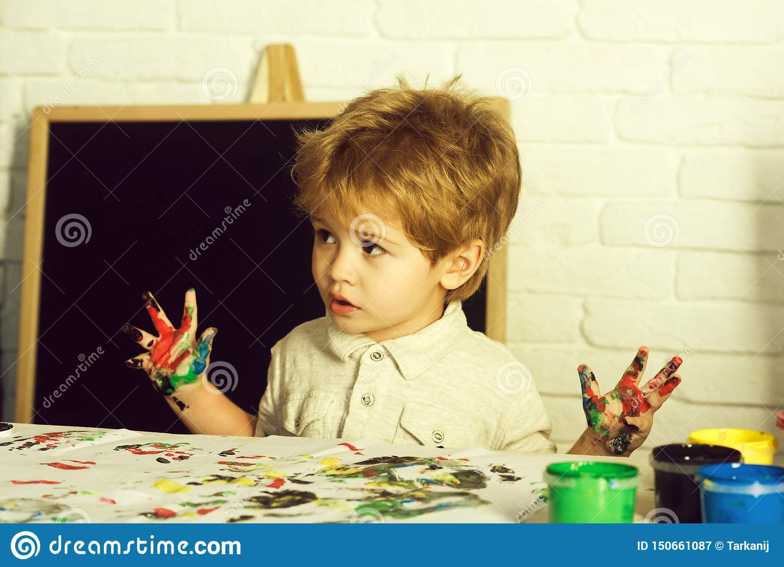 Art therapy. Drawing as a treatment for frustration. The boy draws his fingers. Child with paints.