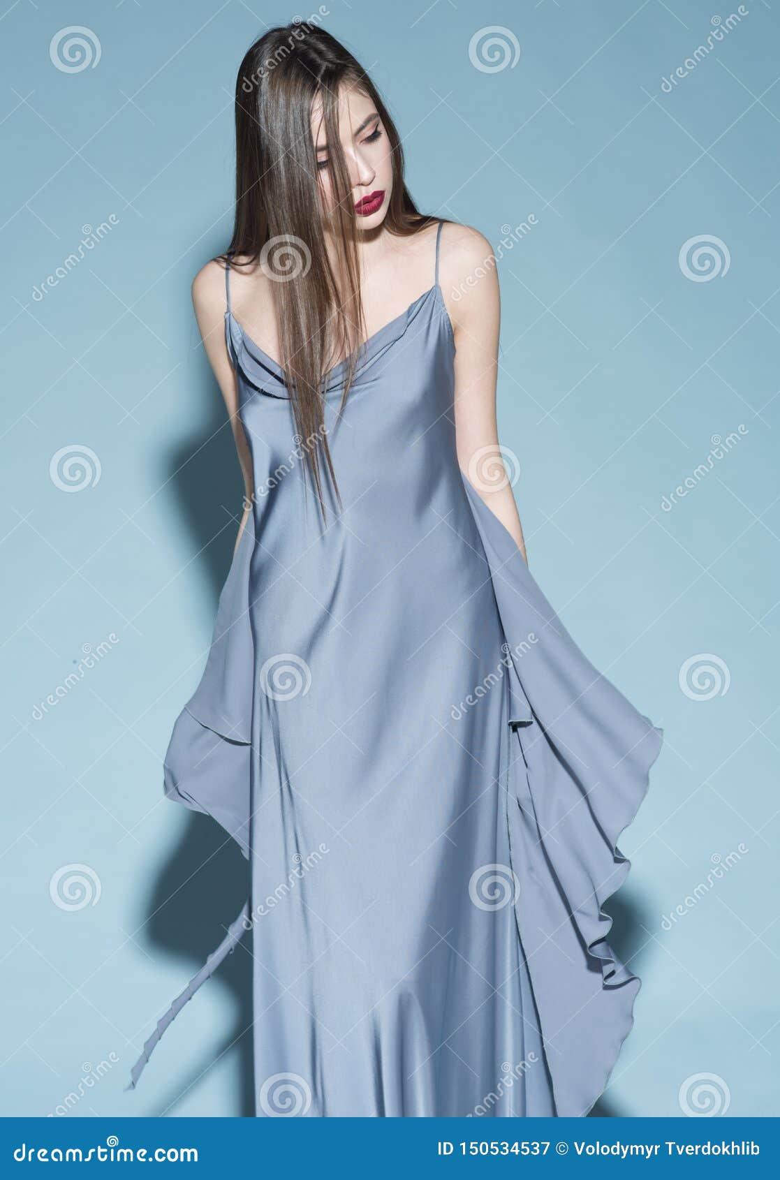Art und Weisekonzept M?dchen auf strengem ?berzeugtem Gesicht im langen blauen Kleid, hellblauer Hintergrund Dame mit den roten L