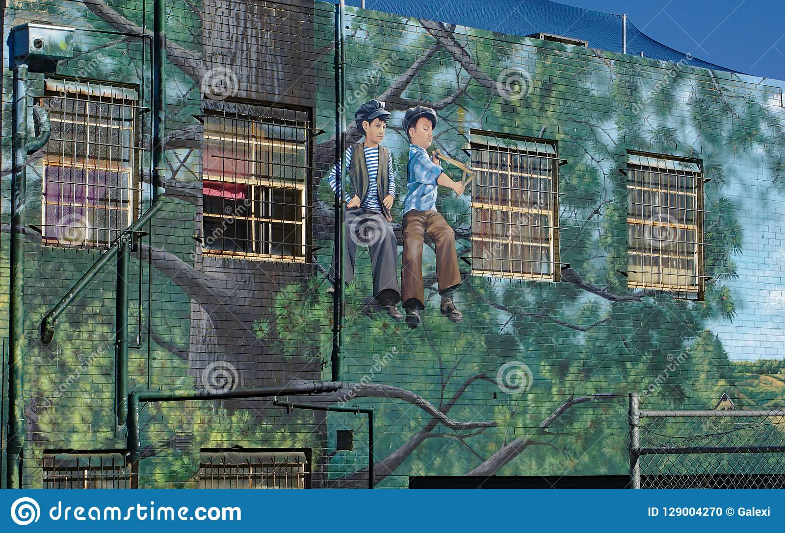 Arte de la calle de dos muchachos que se sientan en árbol en Frankston, Australia