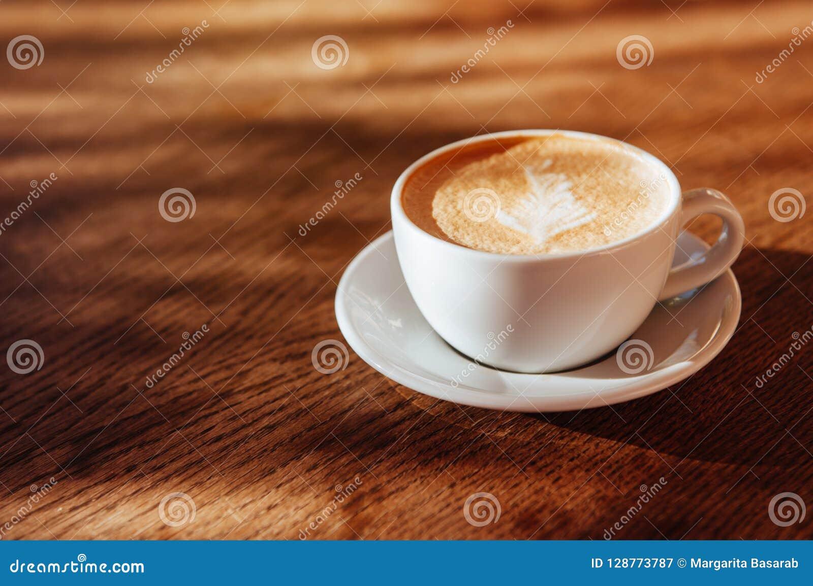 Arte do latte do copo de café no café