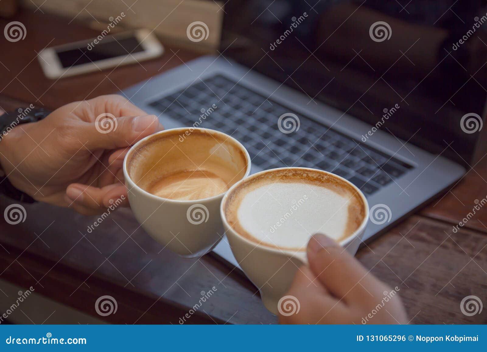 Arte e computer portatile del latte della tazza di caffè sulla tavola con la gente che incontra amicizia insieme al concetto di t