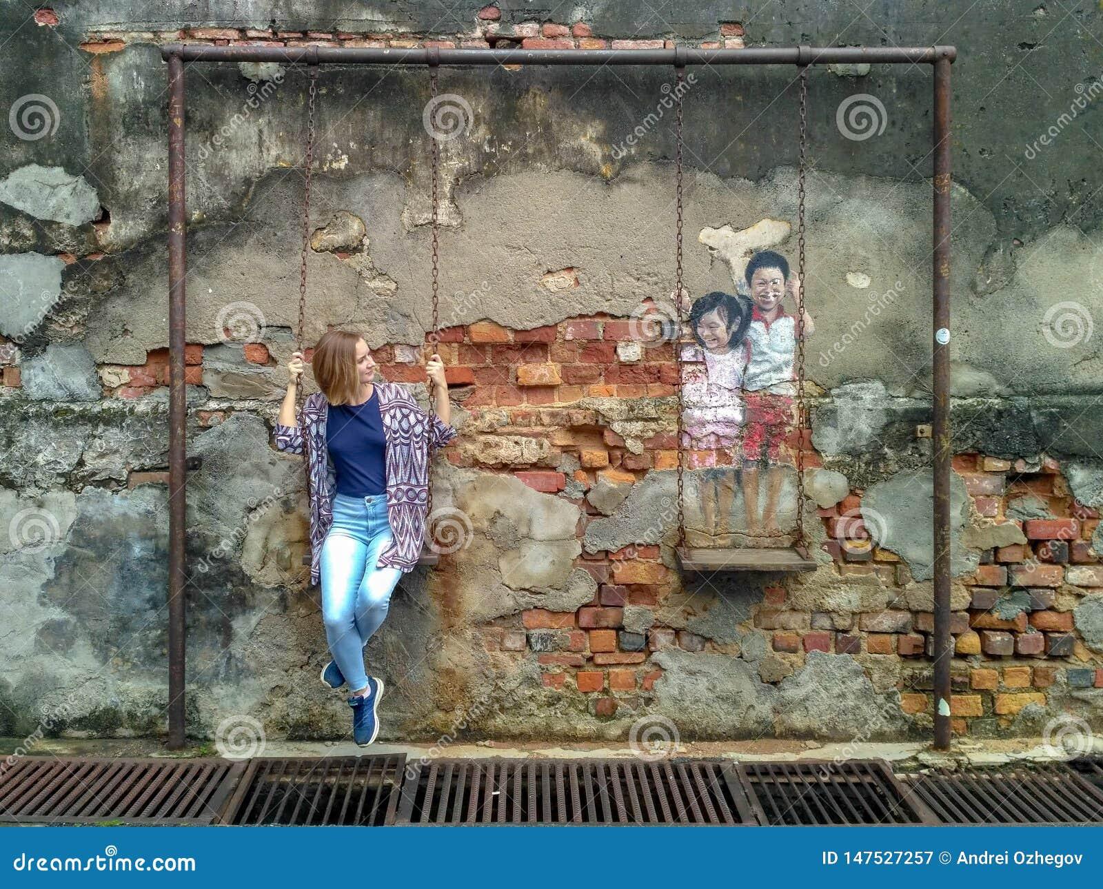 A arte finala da parede chamou 'o irmão e a irmã em um balanço '
