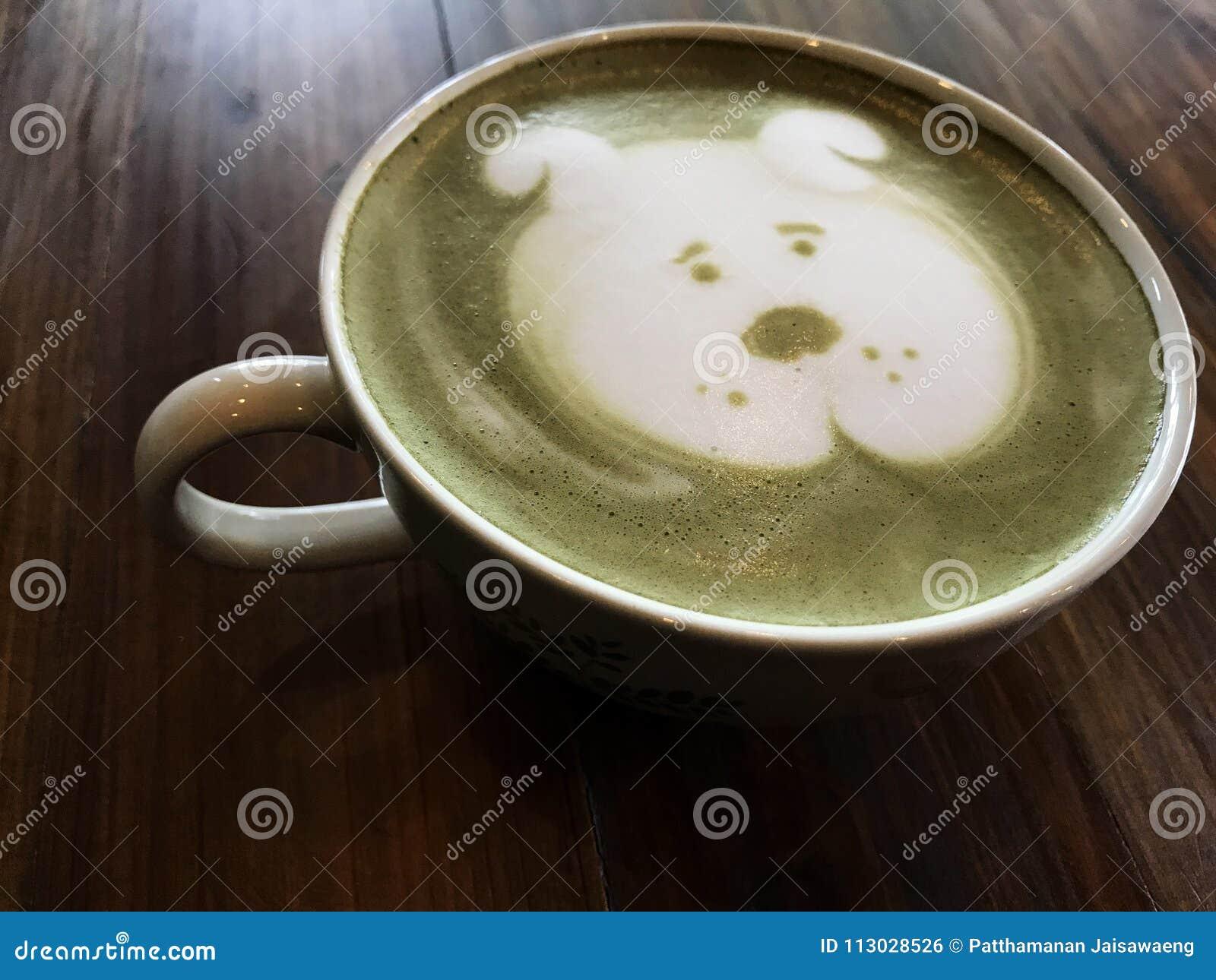 Arte lindo del latte de la cara del perro del té verde en la taza blanca en la tabla de madera