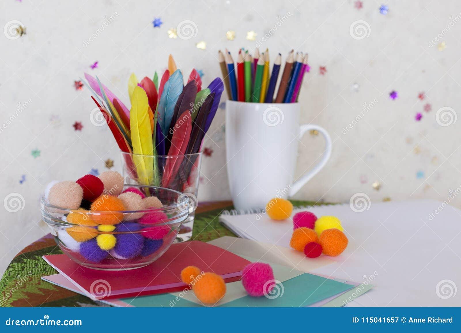Artes da criança e estação de trabalho do ofício com lápis coloridos, as penas coloridas, os poms do pom e o papel