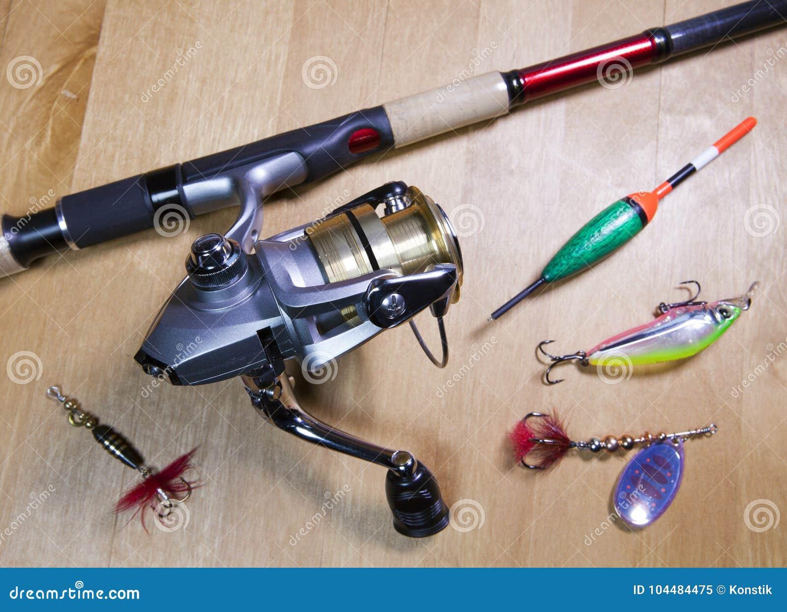 Articles de pêche, bobine, flotteur et amorces sur un fond en bois