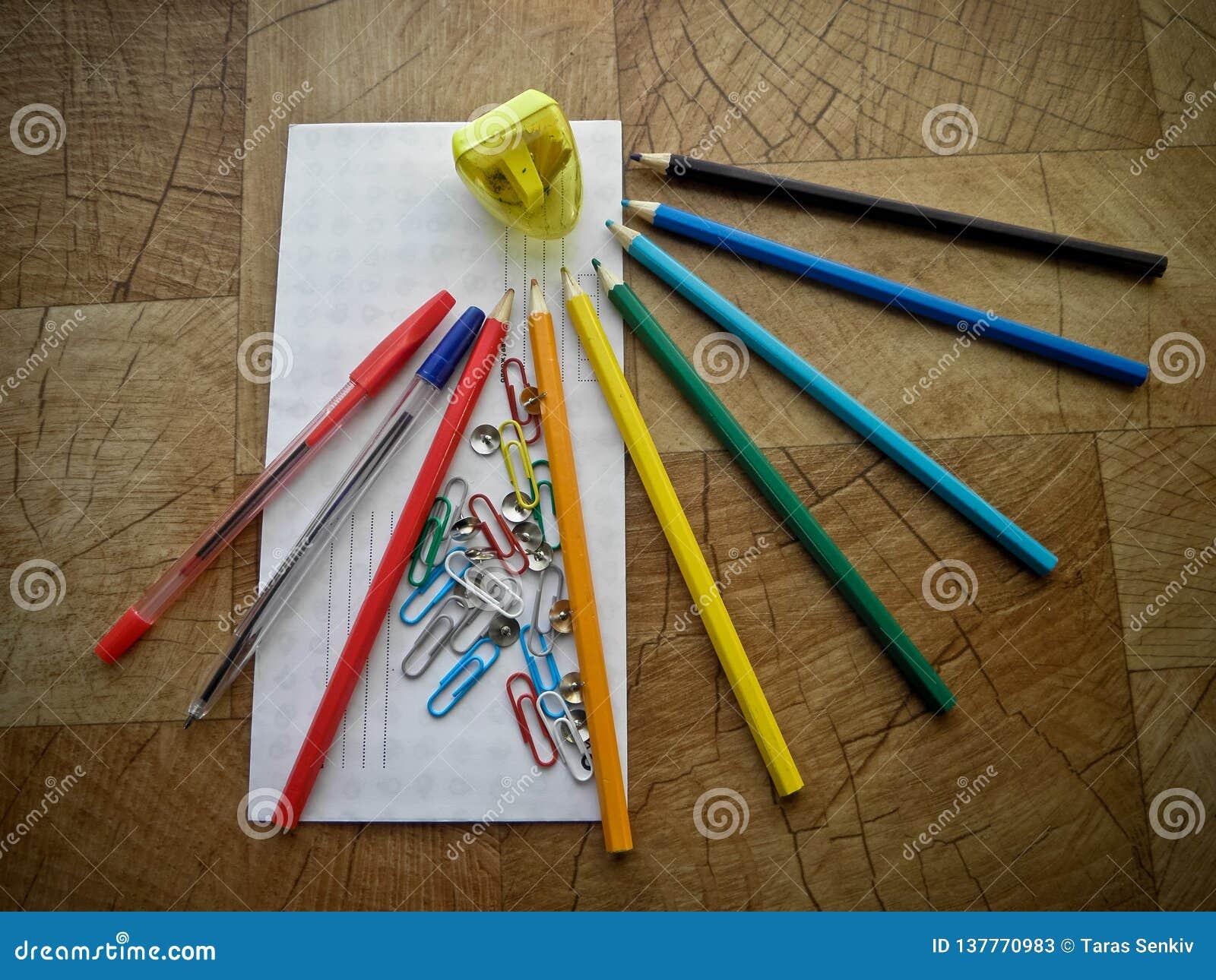 Articoli per ufficio multicolori su una tavola di legno