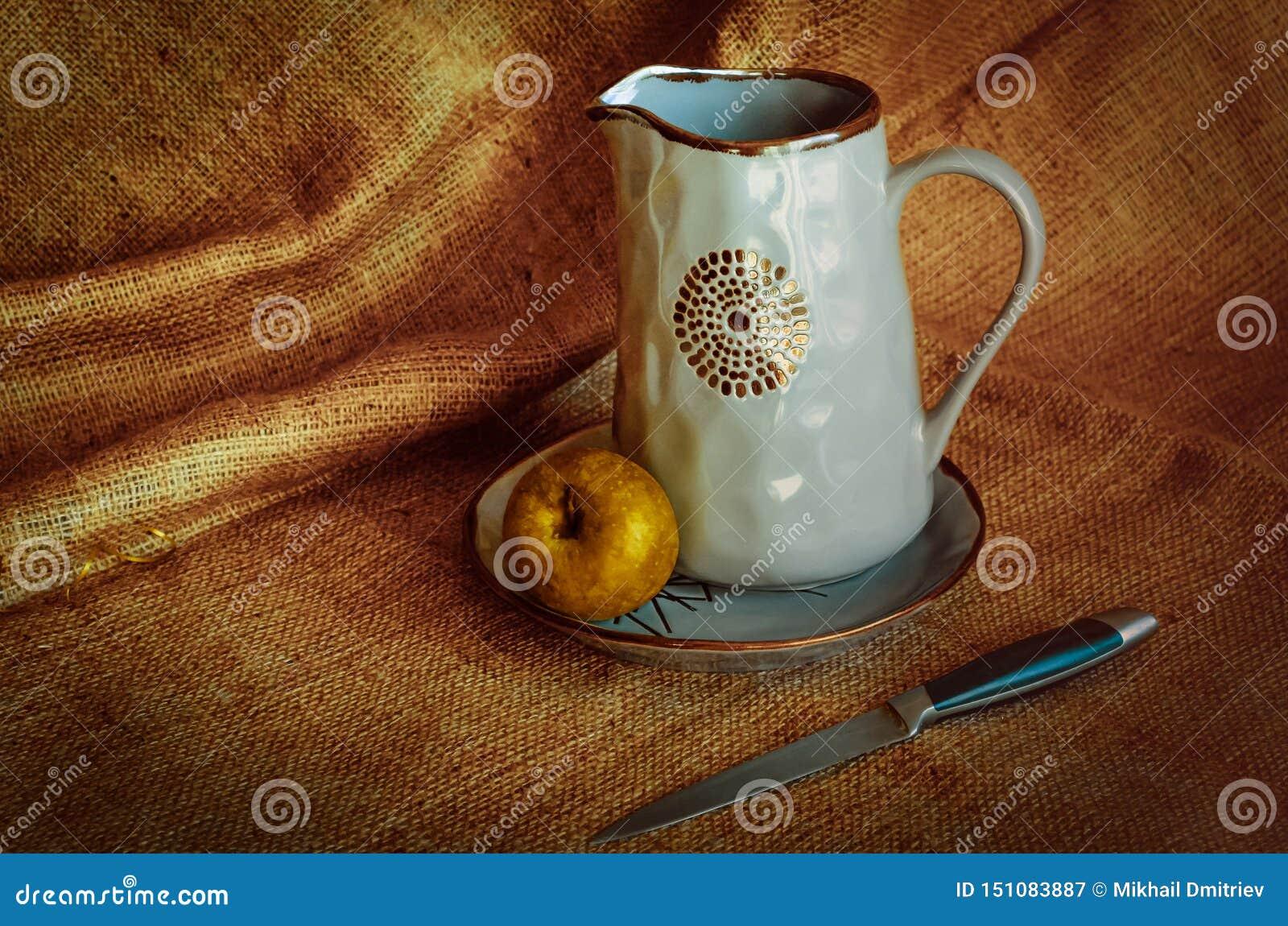 Articolo da cucina per i paesani Nutrmort con le brocche, una mela e un coltello Fondo caldo del tessuto Toni di autunno Stile ru