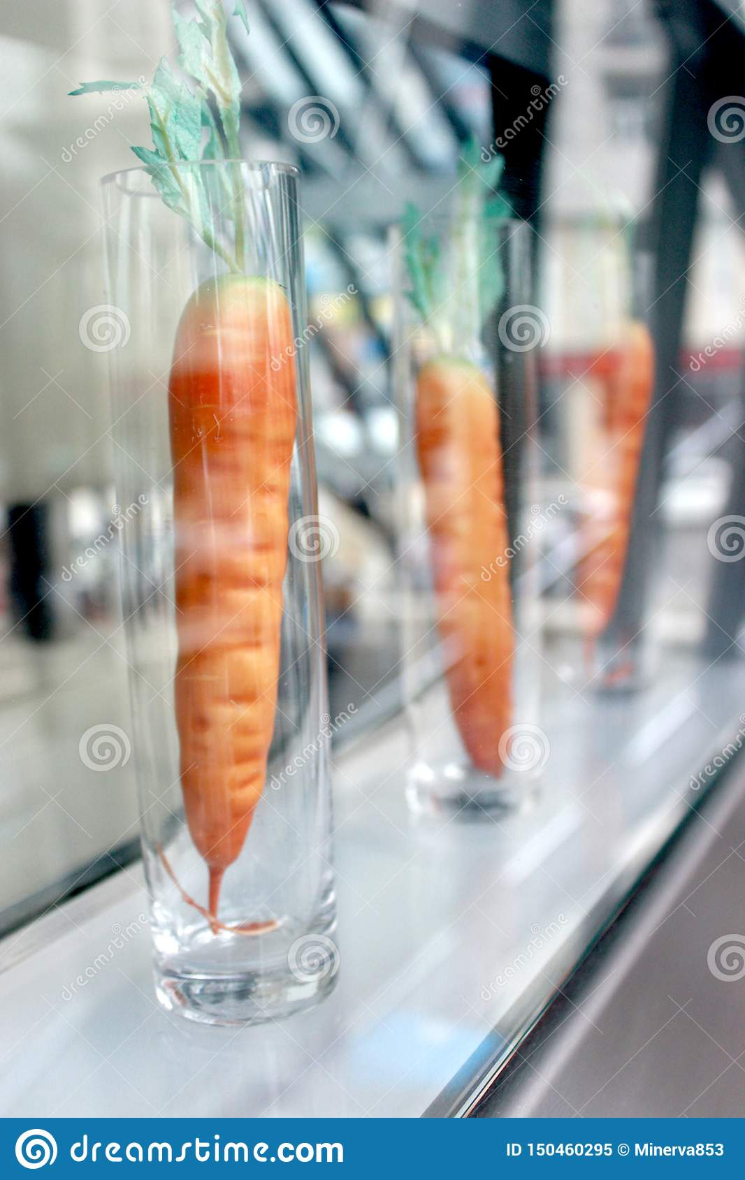 Artificial carrots in long transparent glasses.