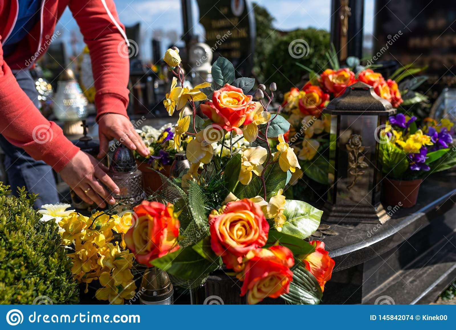 Artificial flowers and candlesticks lie on the tombstone in the cemetery, visible hands of a man.
