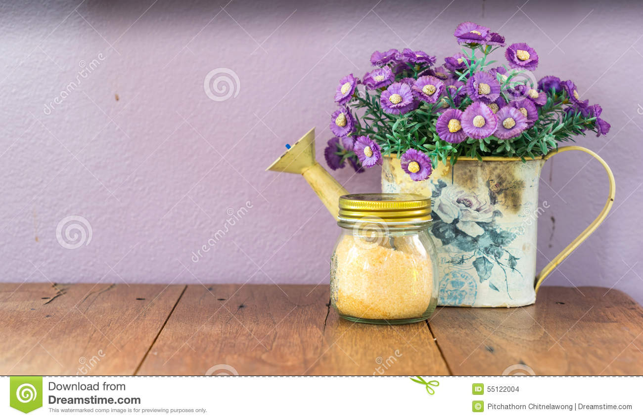 Artificial flowers in vase with sugar jar on table