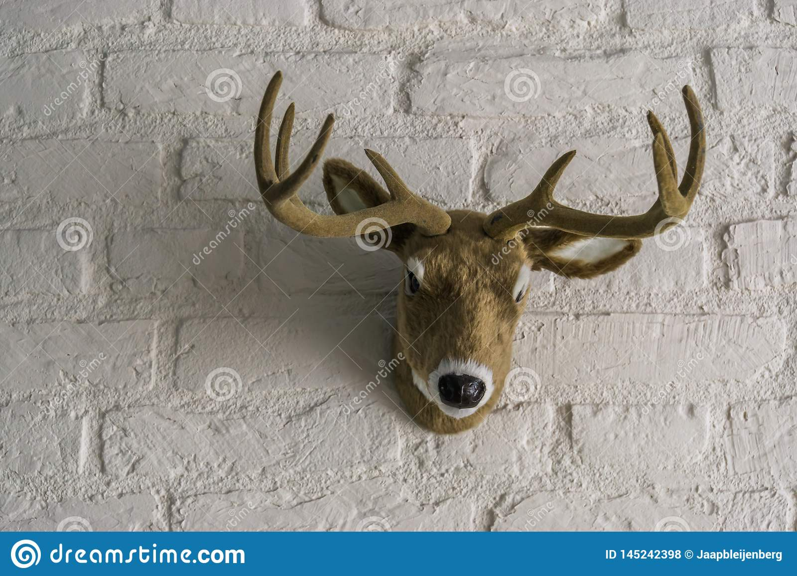 Artificial male deer head with antlers hanging on a white brick wall
