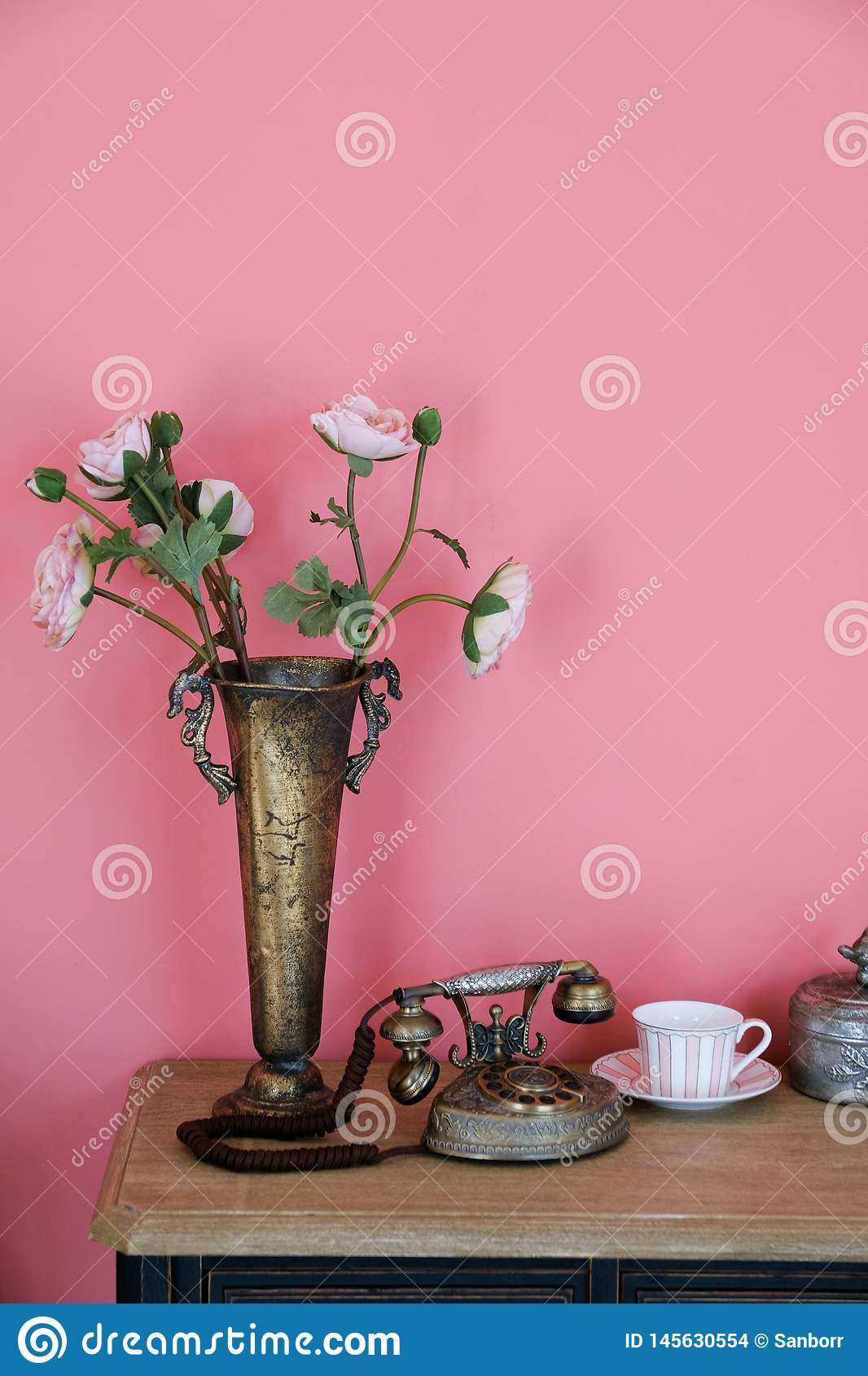 Artificial pink rose flowers in an old iron copper vase on a wooden table, against a pink wall. Near the old phone, a mug on a