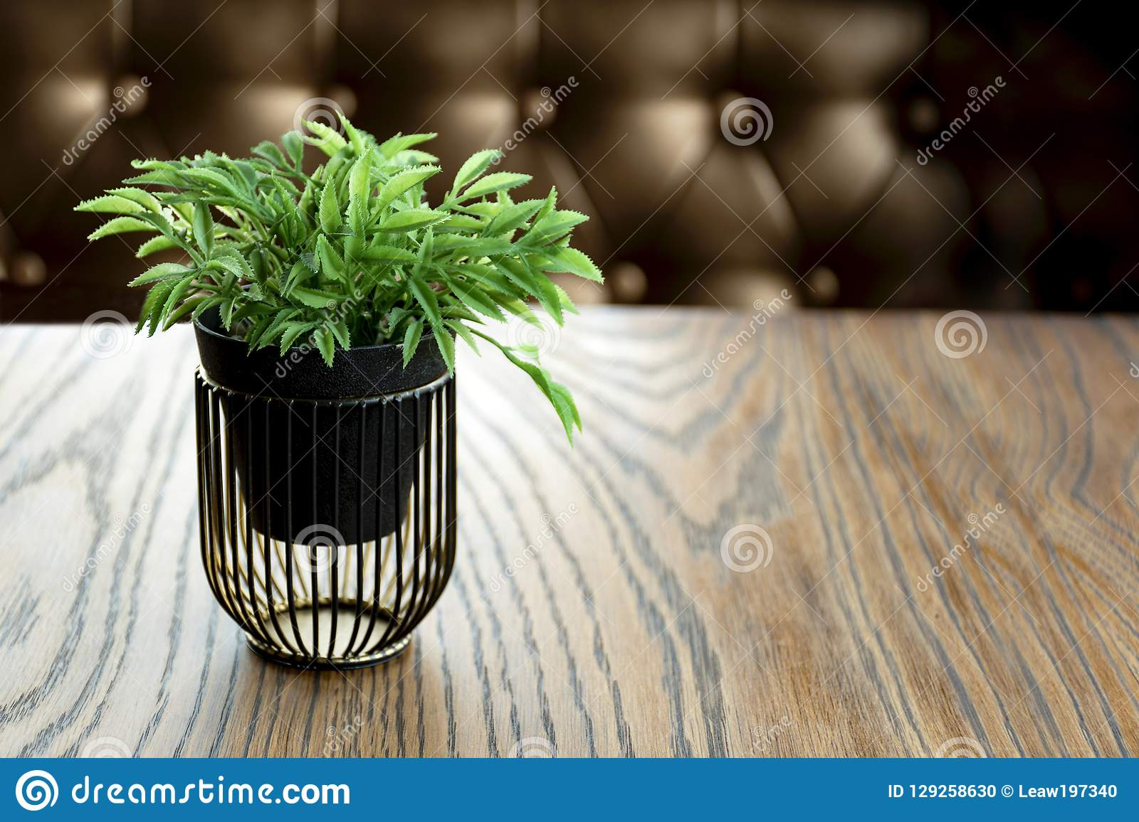 Artificial wood flowerpot on wooden table, small light brown colour in room