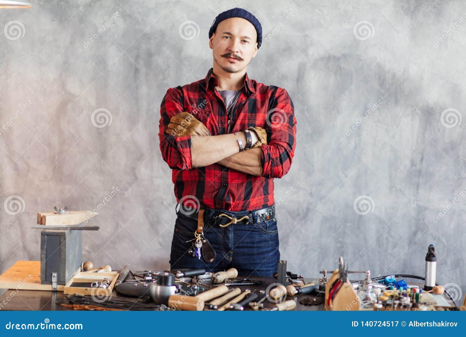 Artigiano sicuro con le armi attraversate che stanno nel luogo di lavoro