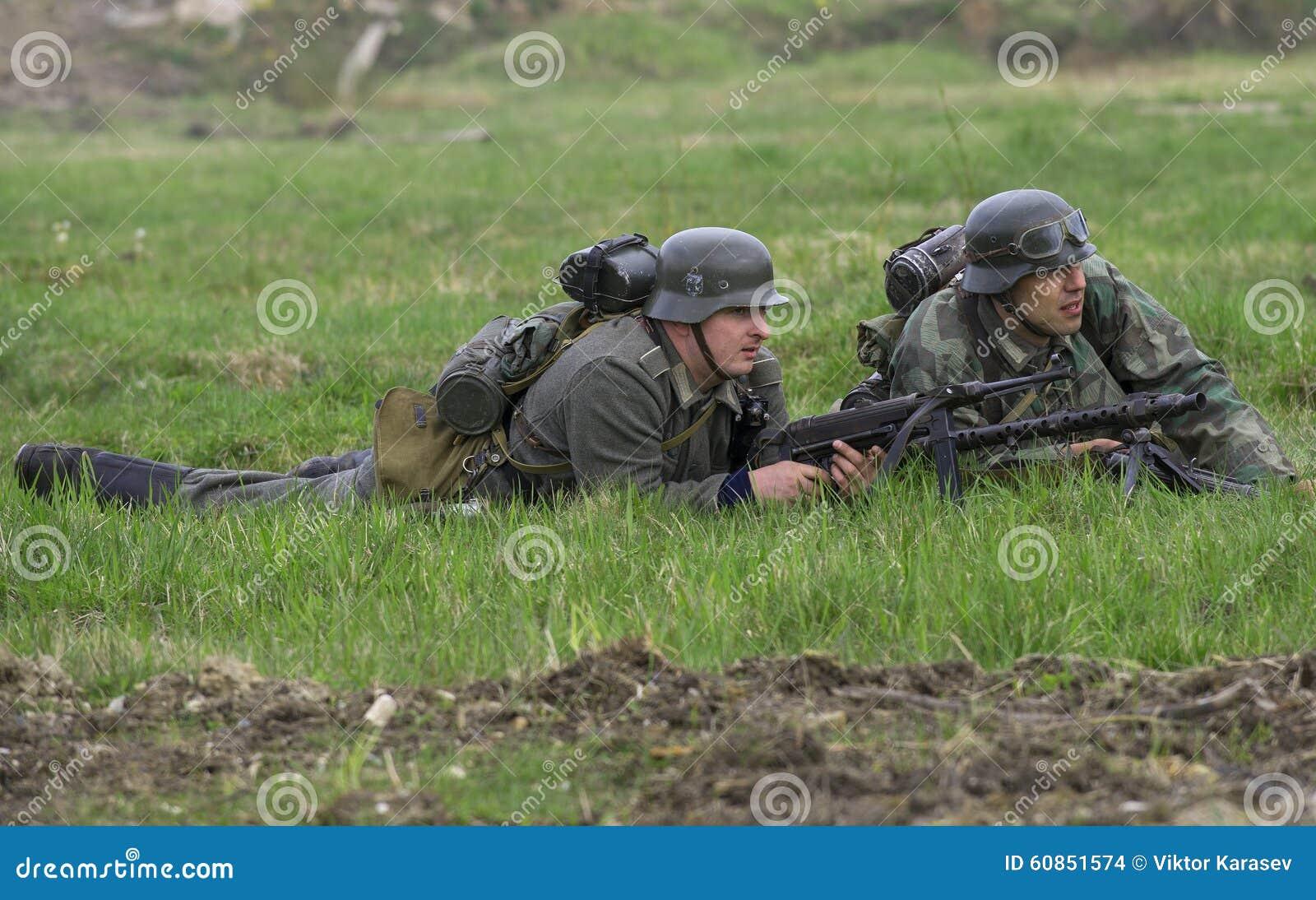 Artillero alemán del soldado de infantería y de máquina con una ametralladora que miente en la hierba Reconstrucción del episodio