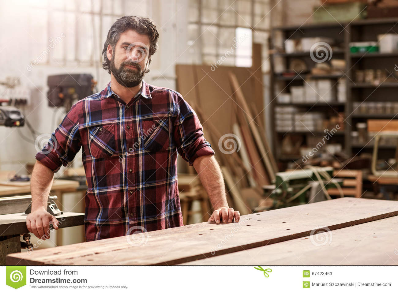 Artisan craftsman with a beard in his woodwork workshop for Craftsman workshop