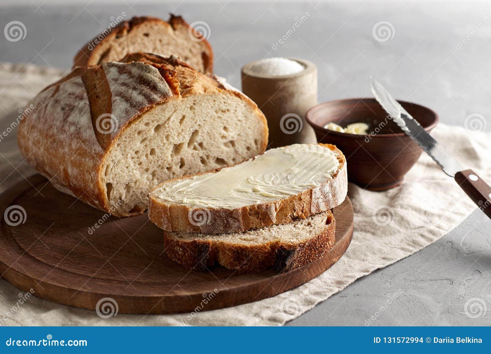 Artisanaal gesneden toostbrood met boter en suiker op houten scherpe raad Eenvoudig ontbijt op grijze concrete achtergrond