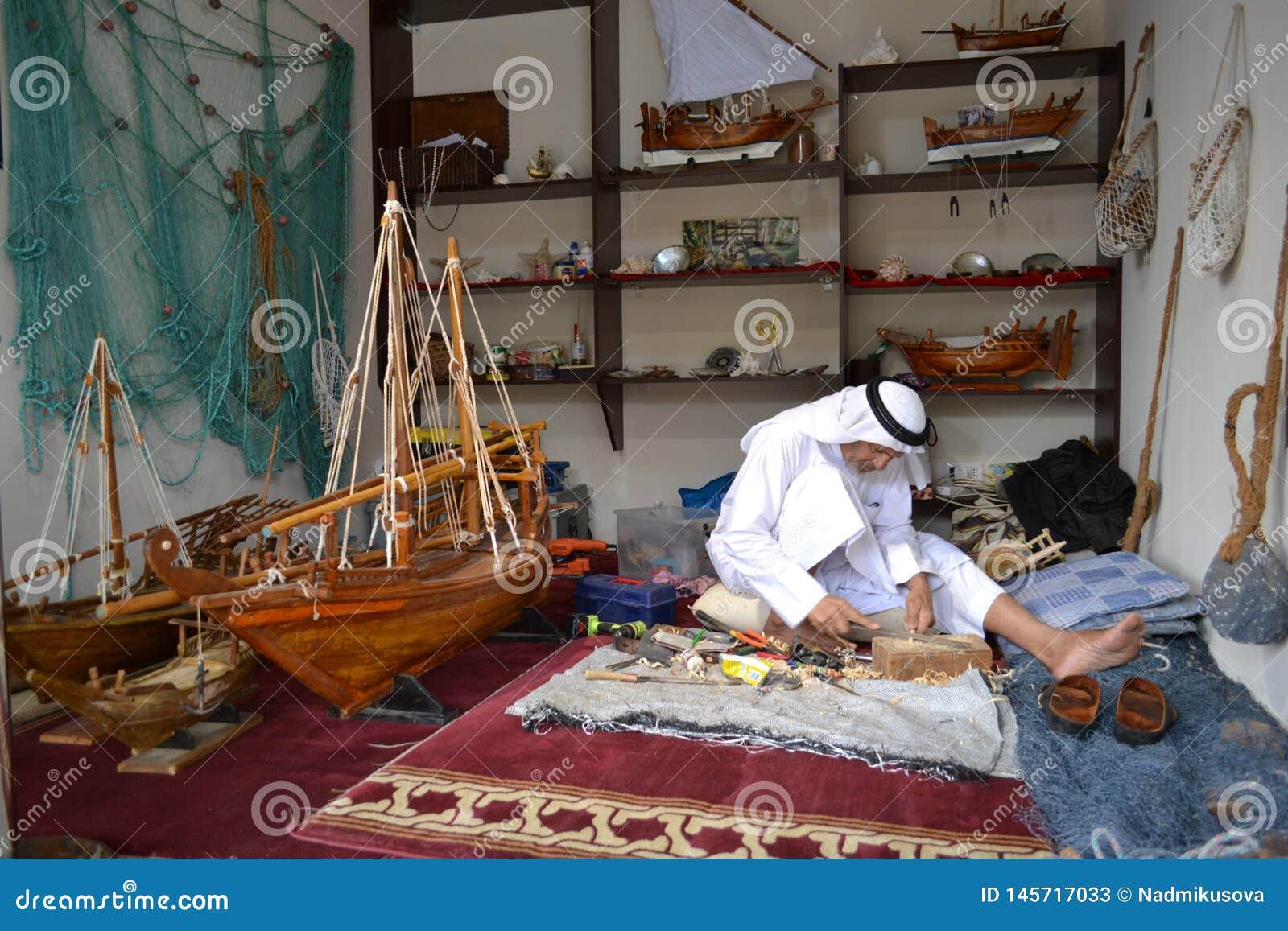 Artisanaal van Qatar dat in traditionele kleren met de hand gemaakt houten model van schepen creeert