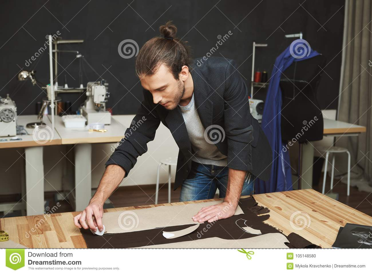 Artist creating masterpiece. Close up of young beautiful male clothes designer with trendy hairstyle and fashionable