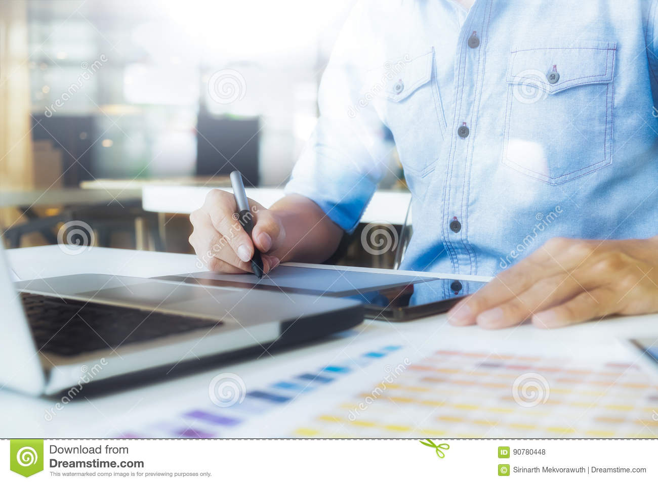 Artist drawing on graphic tablet with color swatches in office.