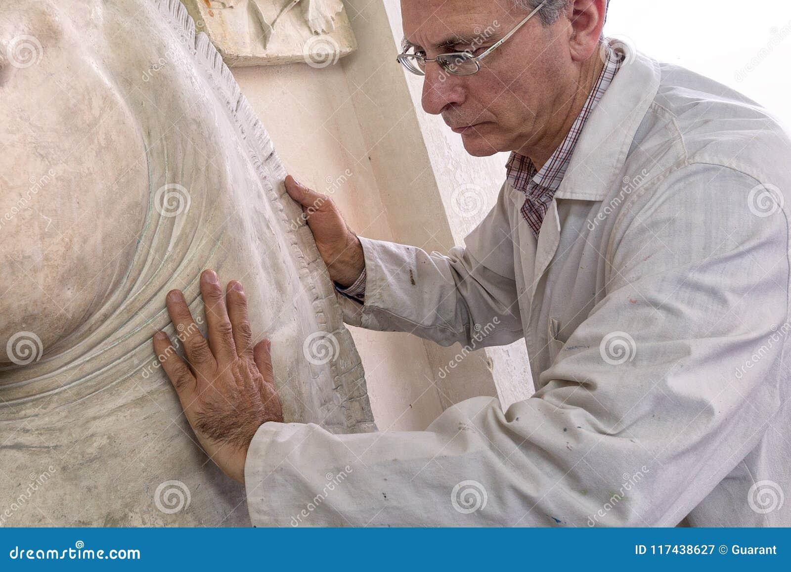 Artist gesture with hands on a sculpture in arts studio