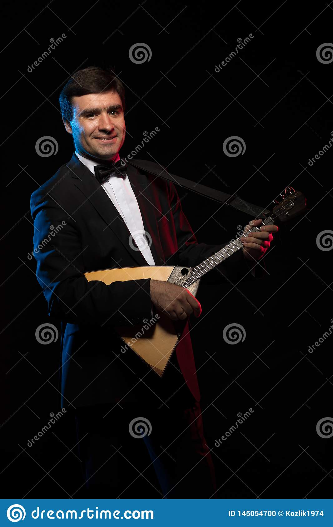 Artist musician, a dark-haired man in a black suit and a bow tie, plays a balalaika