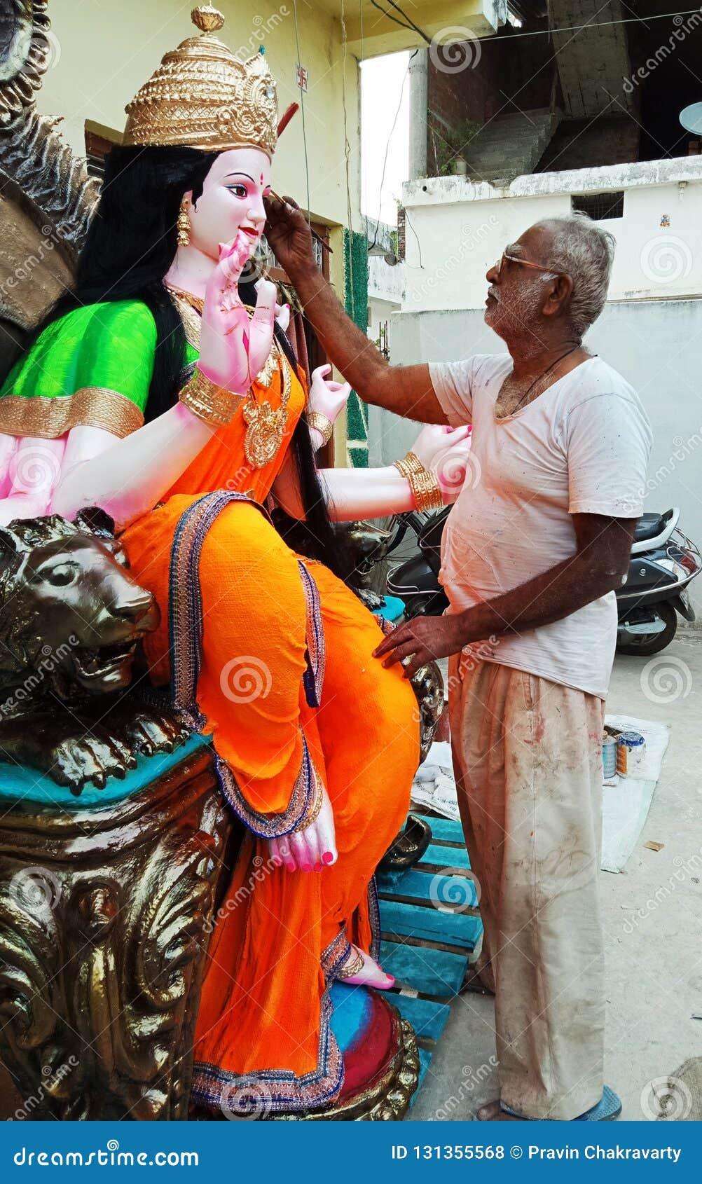 An artist painted on a sculpture of goddess Durga. Indian festival.