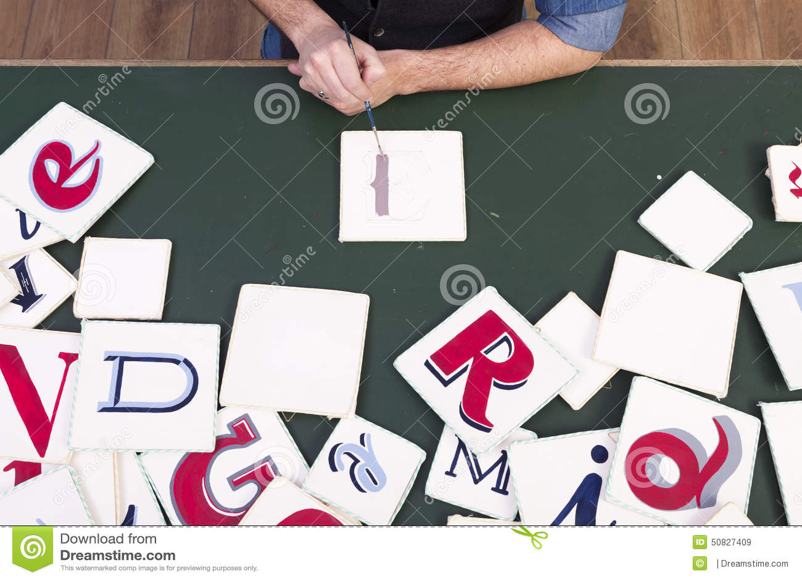 Artist painting colors handwritten letters. Calligraphy. Desk ba