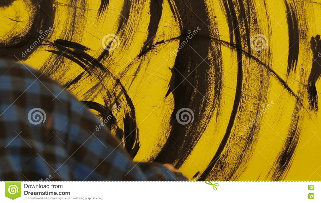 Artist Paints The Abstract Ornament With Black Brush On Yellow Wall ...