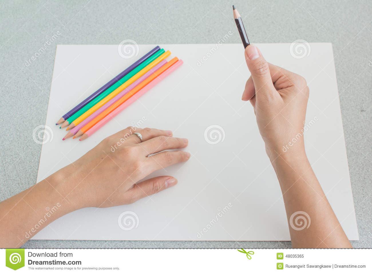 Artist preparing to sketch with colored pencil crayons close up high angle view of his hands holding a pencil with the rest of the set lying on a large