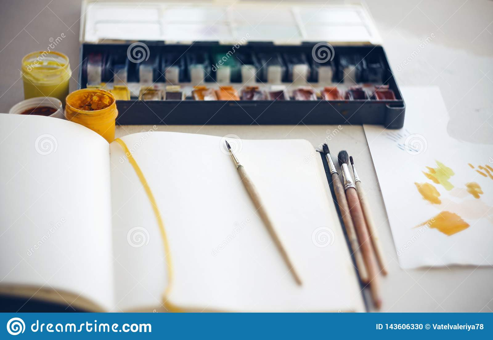 The artist`s Desk on which sketchbook, brushes, watercolor and gouache paints