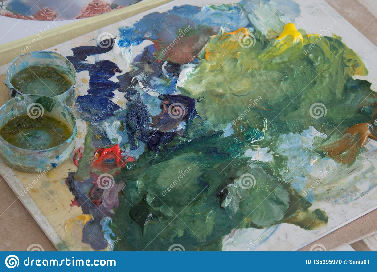 The artist`s palette, mixed oil paint on the Board. creative mess on the table. preparation for the drawing process