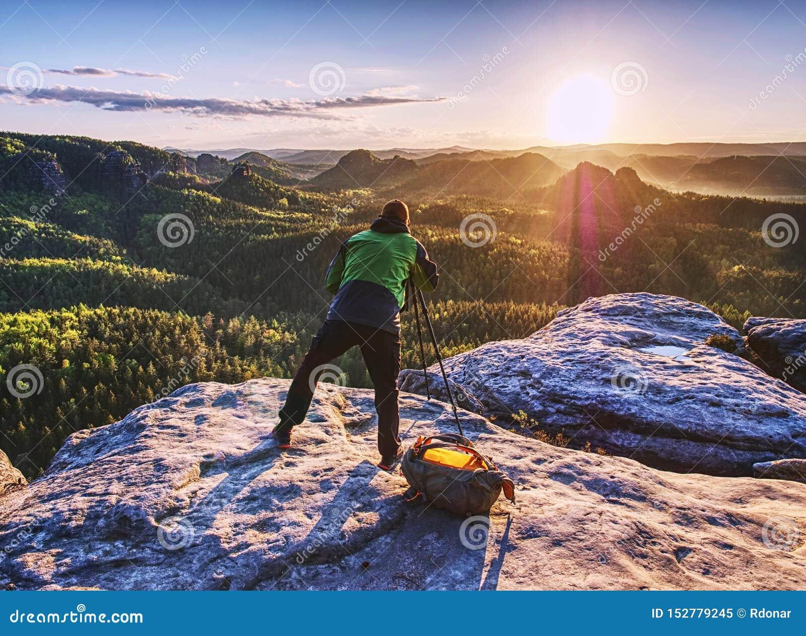 Artist set camera and tripod to photograph sunrise on summit