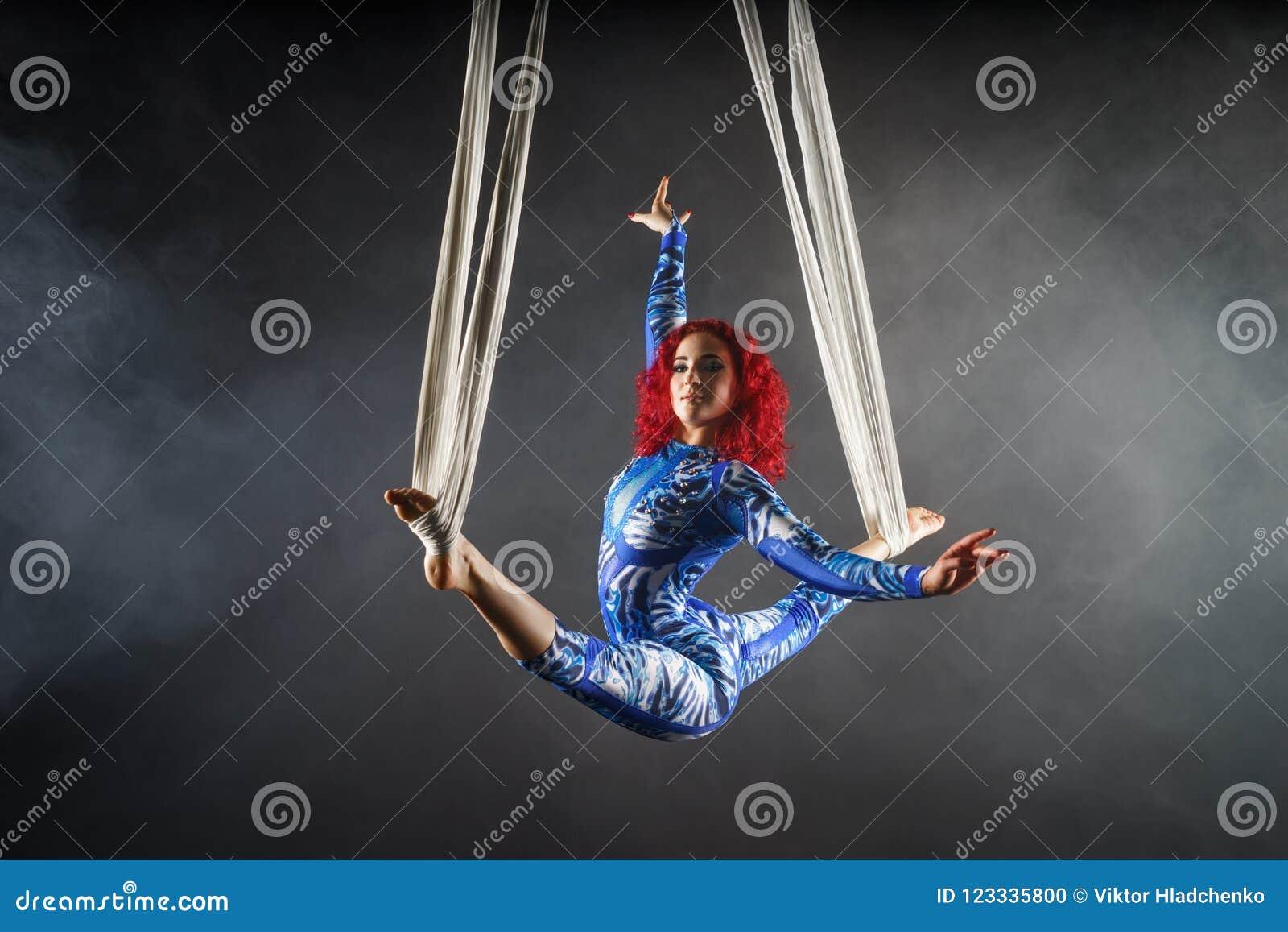 Artista aéreo  sexy  atlético do circo com o ruivo na dança azul do traje no ar com equilíbrio