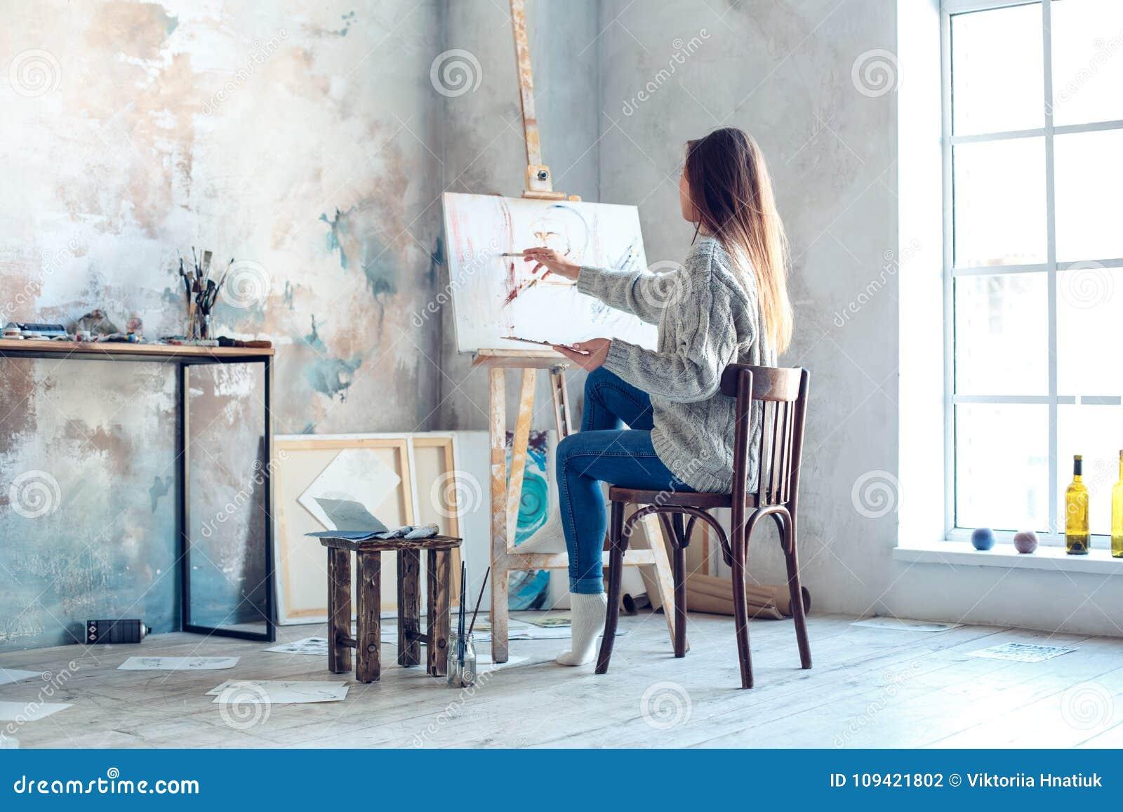 Artista da jovem mulher que pinta em casa a vista traseira de pintura criativa