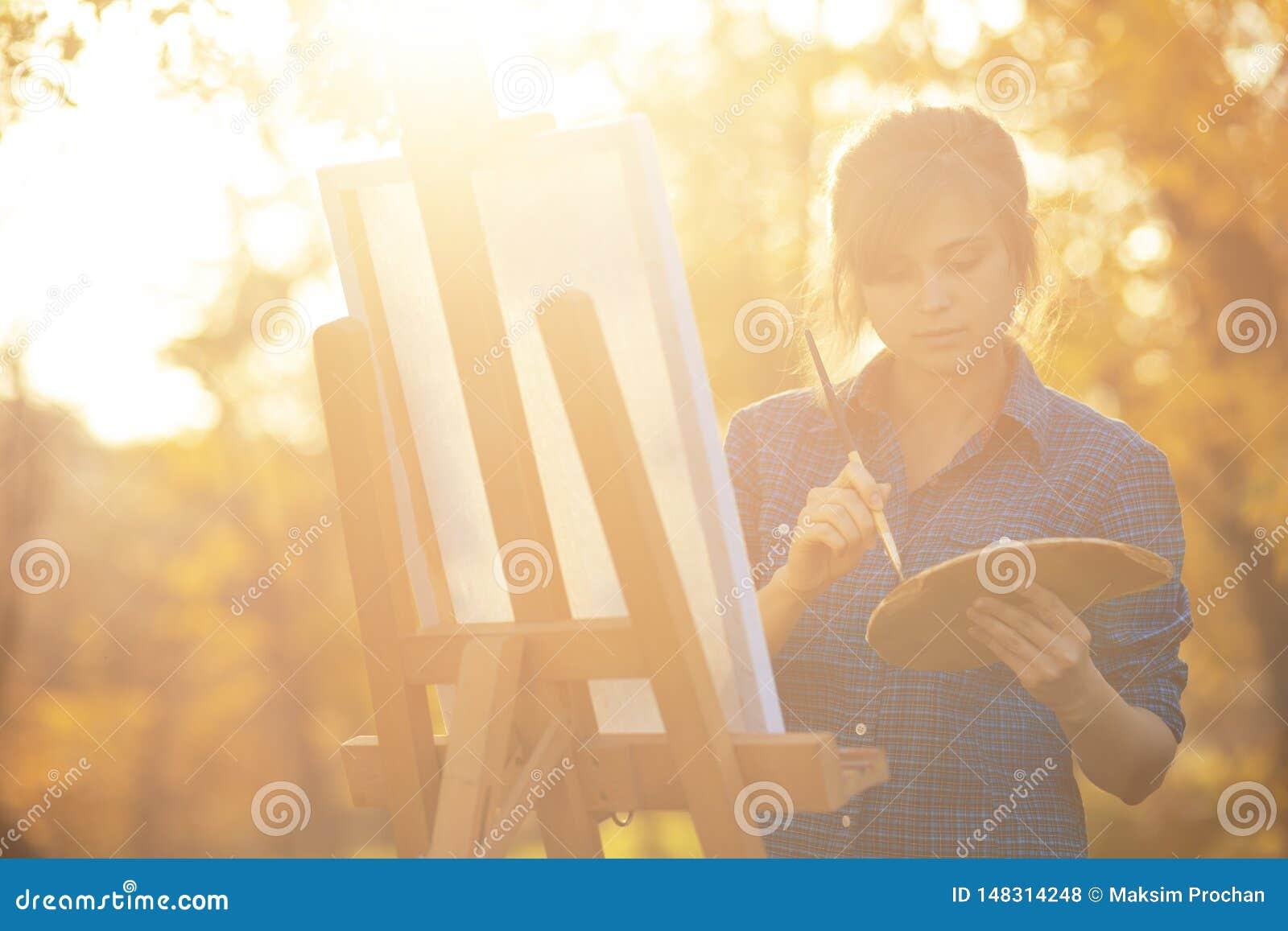 Artista da jovem mulher que tira uma imagem na lona em uma arma??o na natureza, em uma menina com uma escova e em uma paleta das
