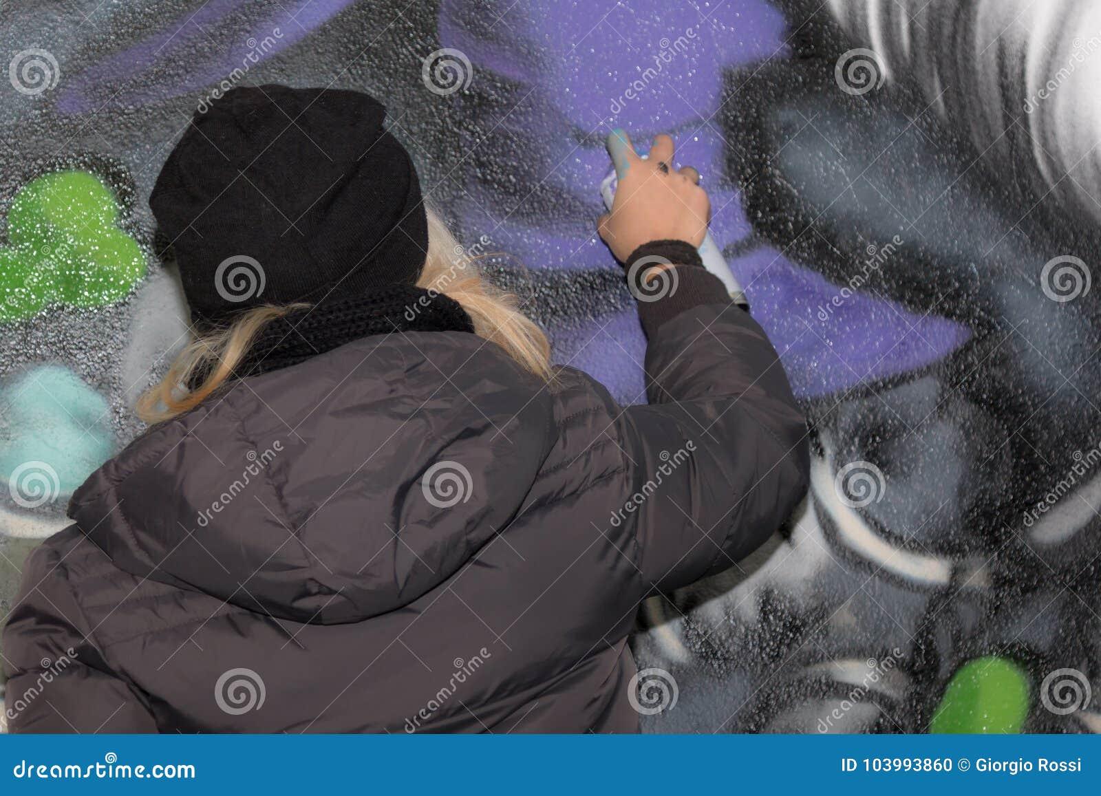 Artista da rua da moça: Pulverização na parede urbana pública da cidade
