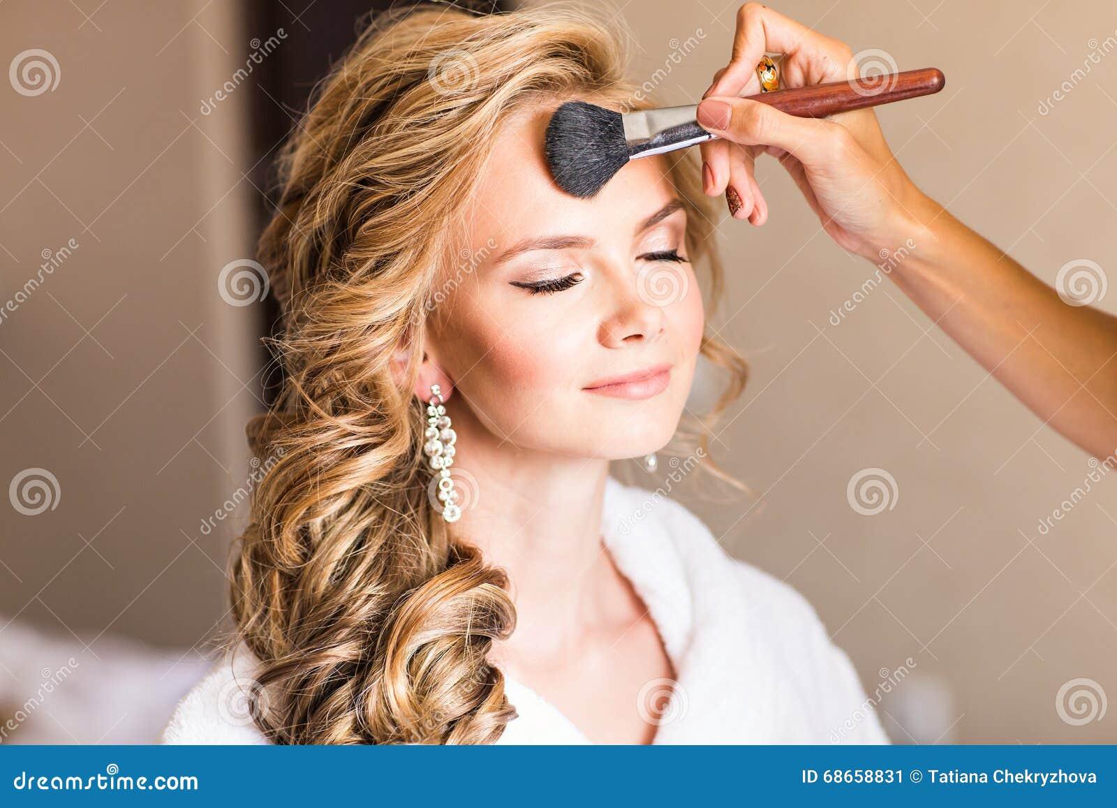 Artista de maquillaje de la boda que hace a una novia del compensar Muchacha modelo atractiva hermosa dentro Mujer rubia de la be
