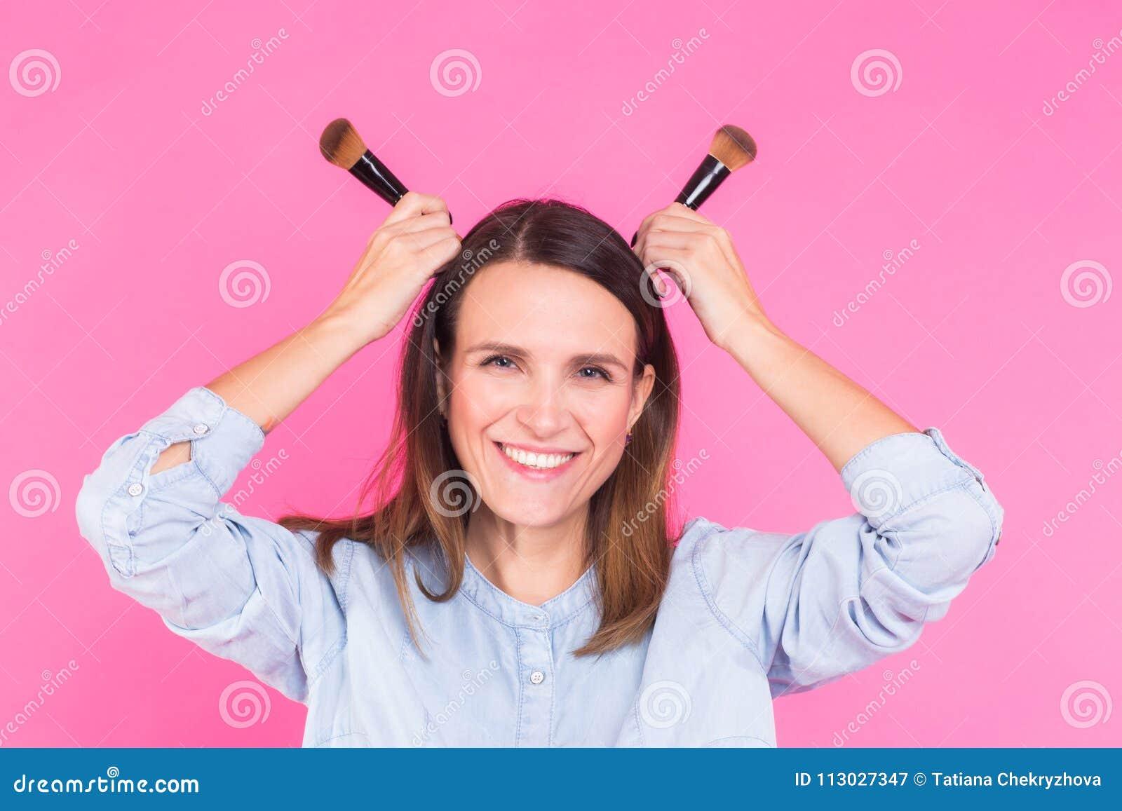 Artista de maquillaje divertido con los cepillos en fondo rosado