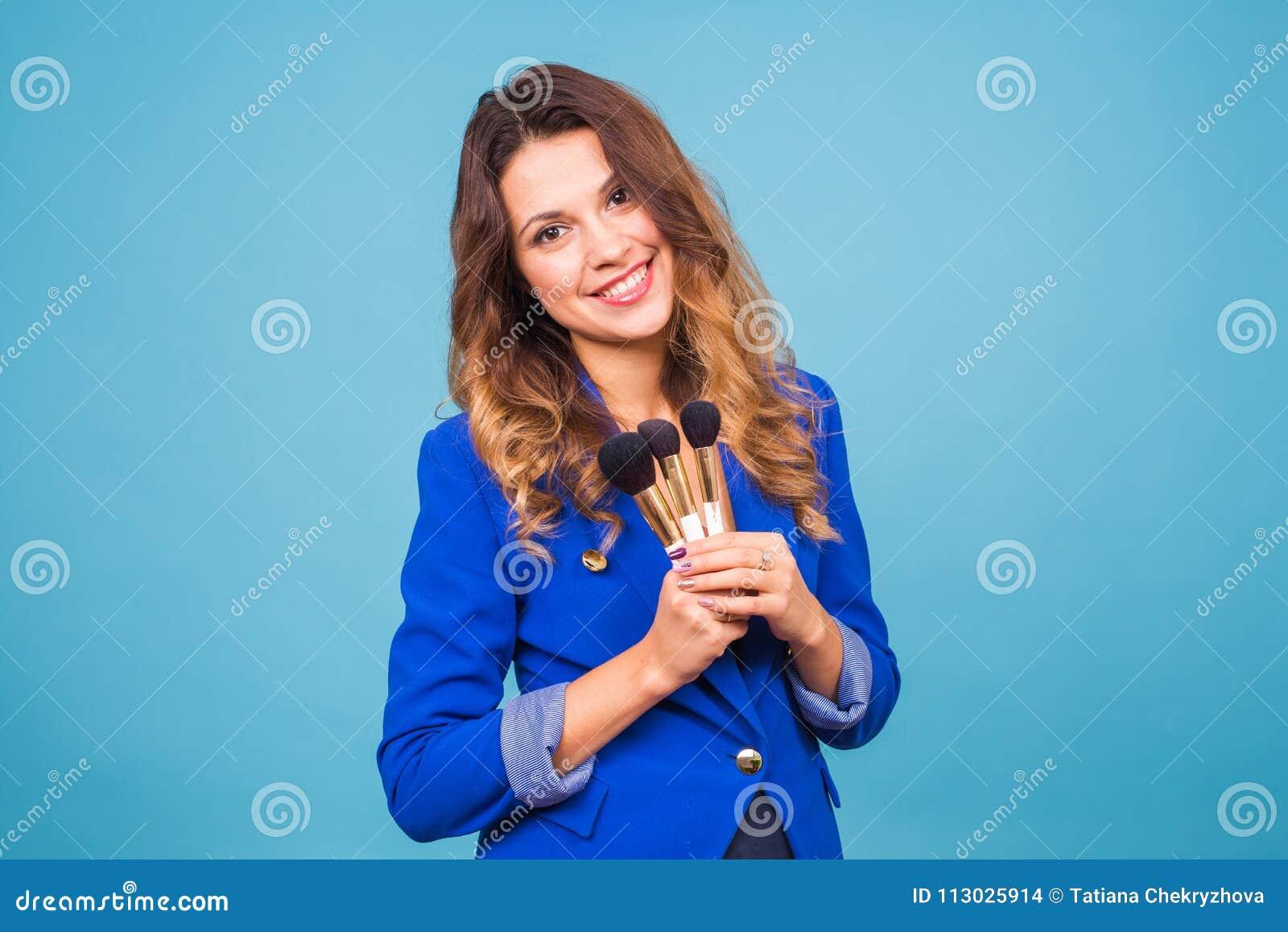Artista de maquillaje hermoso con los cepillos en fondo azul