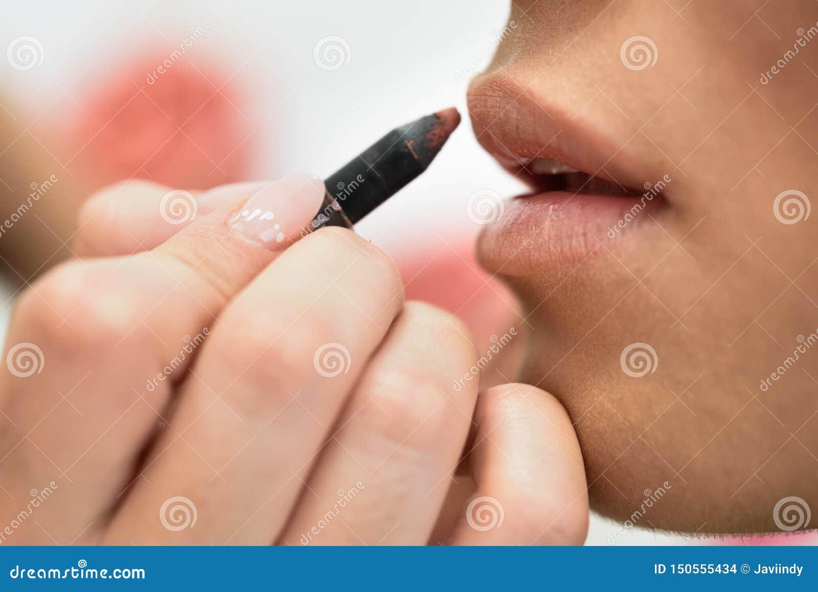Artista de maquillaje que compone los labios de una mujer joven africana