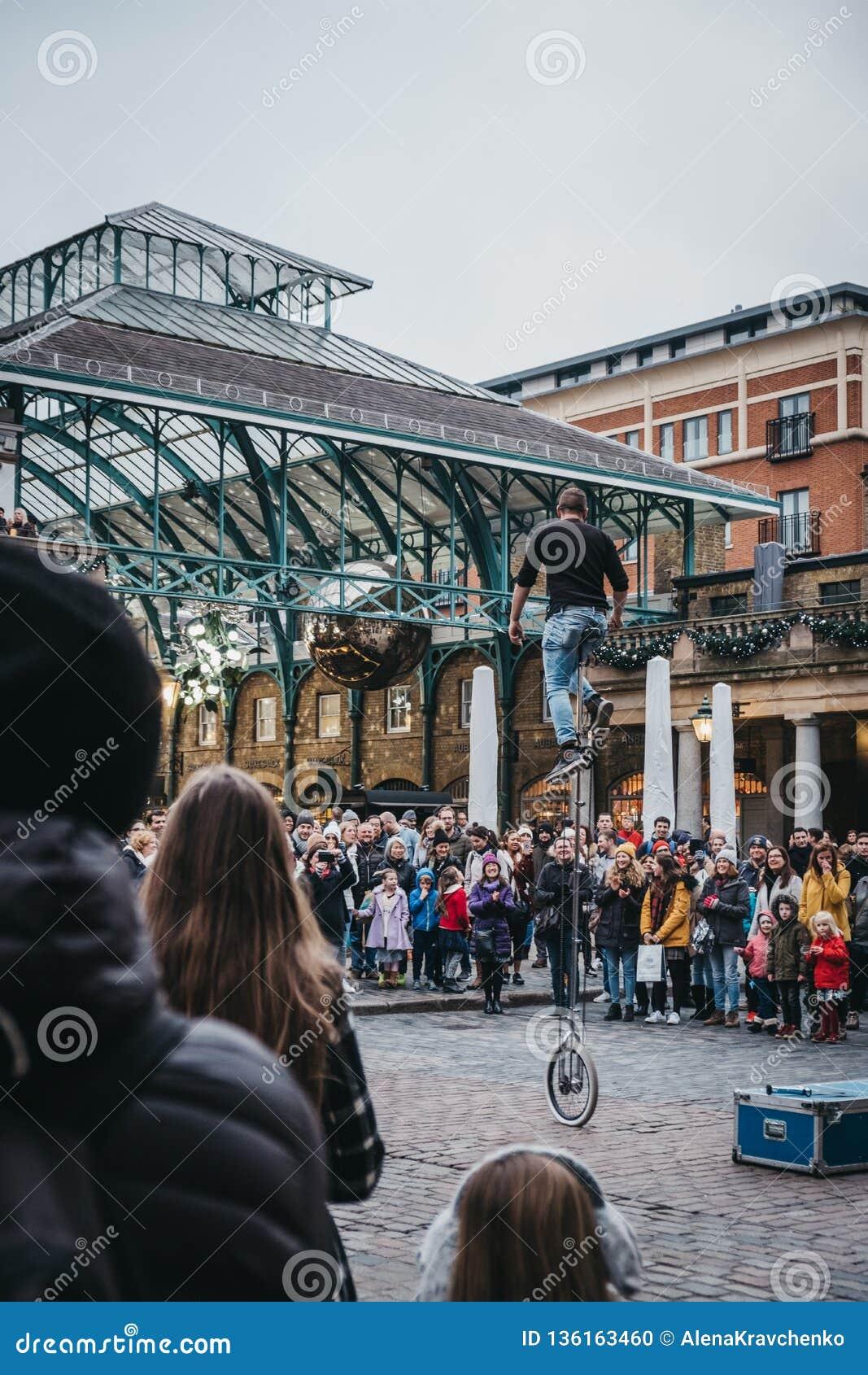 Artista de observación de la calle de la muchedumbre que se realiza delante del mercado de Covent Garden, Londres, Reino Unido