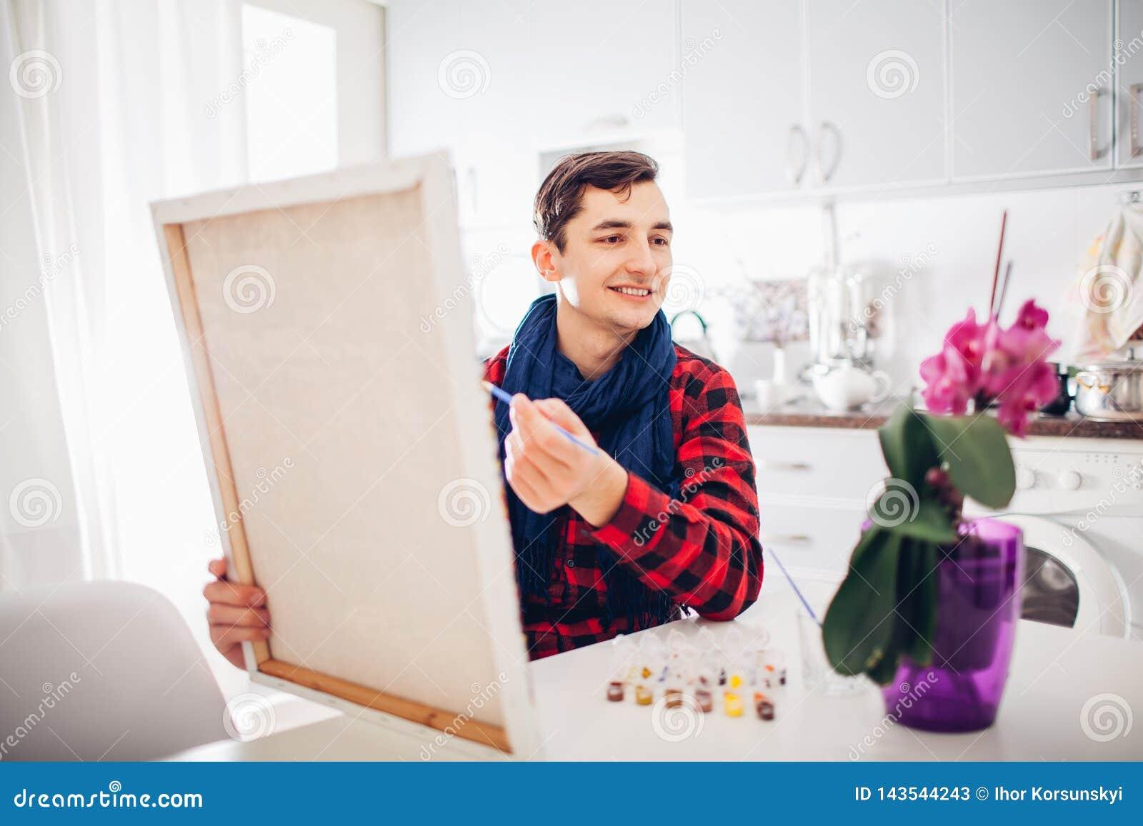 Artista del hombre joven que pinta en casa la pintura creativa