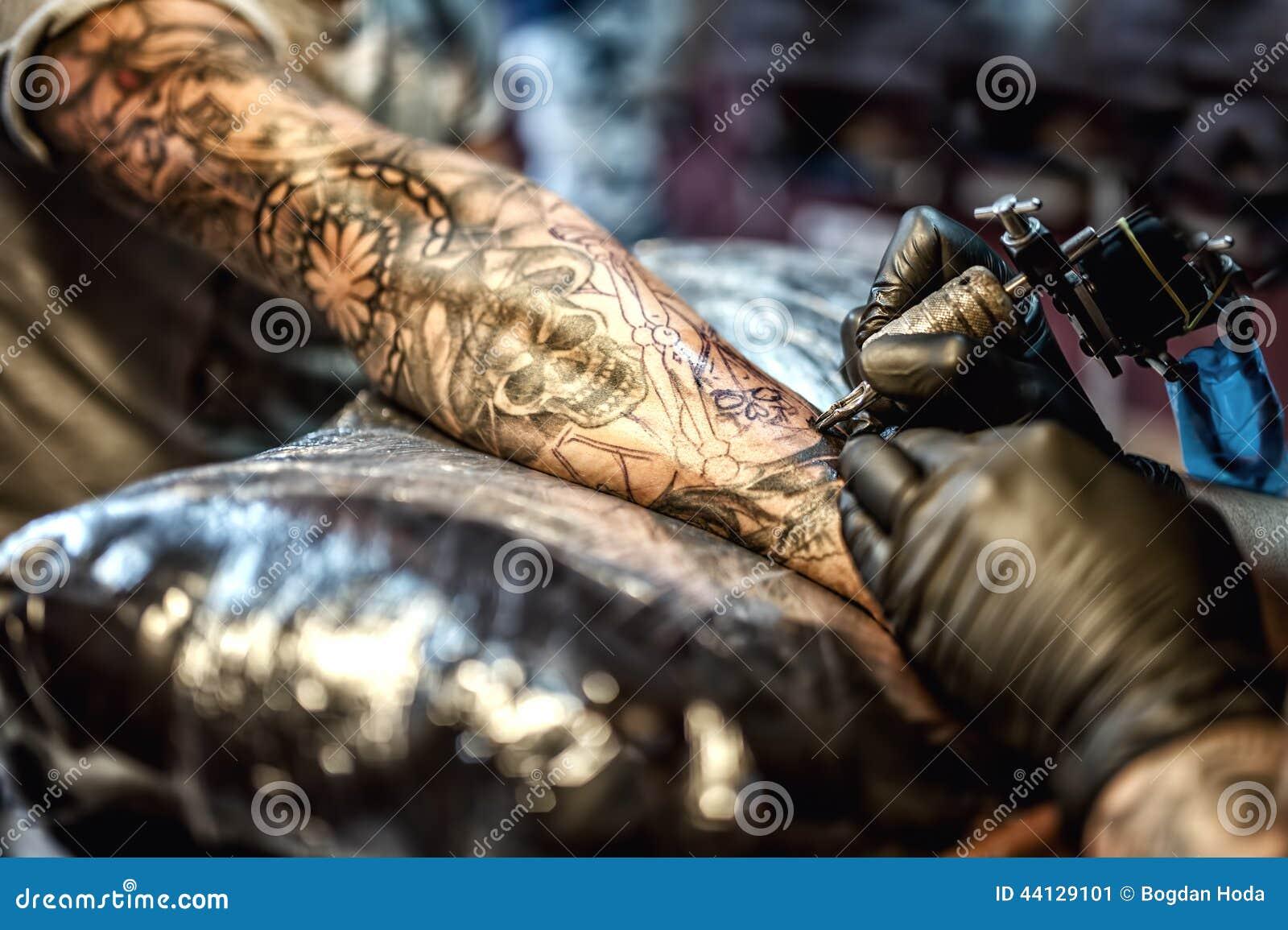 Artista del tatuaggio che attinge braccio e su pelle del cliente