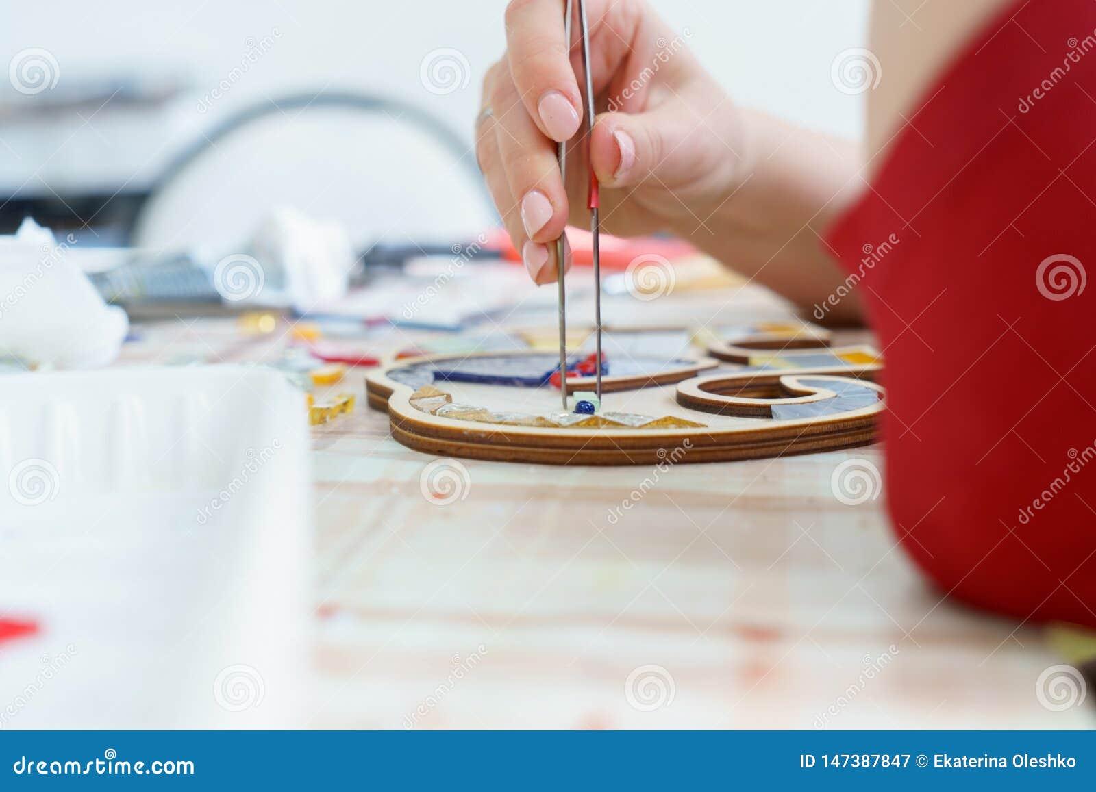 Artista femminile delle mani raccogliere mosaico vicino su