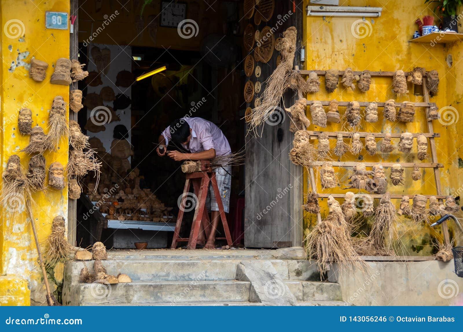Artista que cinzela as cabeças humanas feitas de raizes de madeira