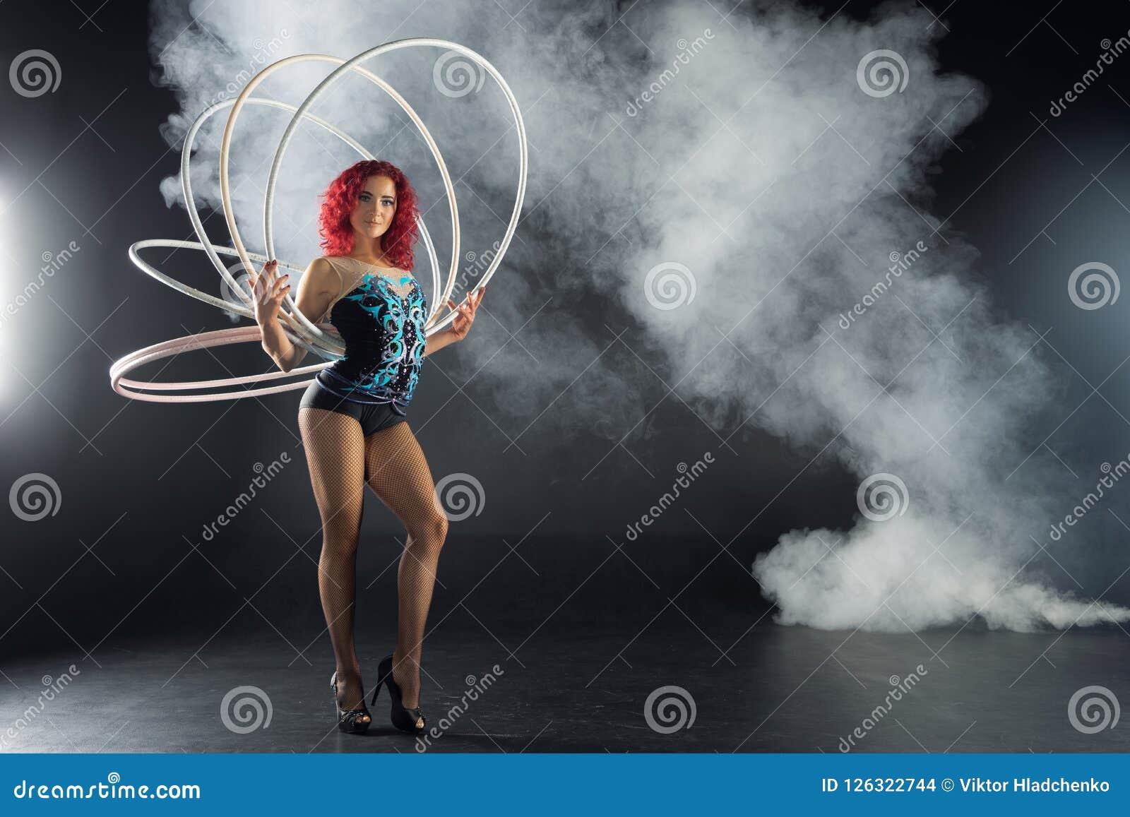 Artista vermelho fêmea bonito do circo do cabelo que guarda aros