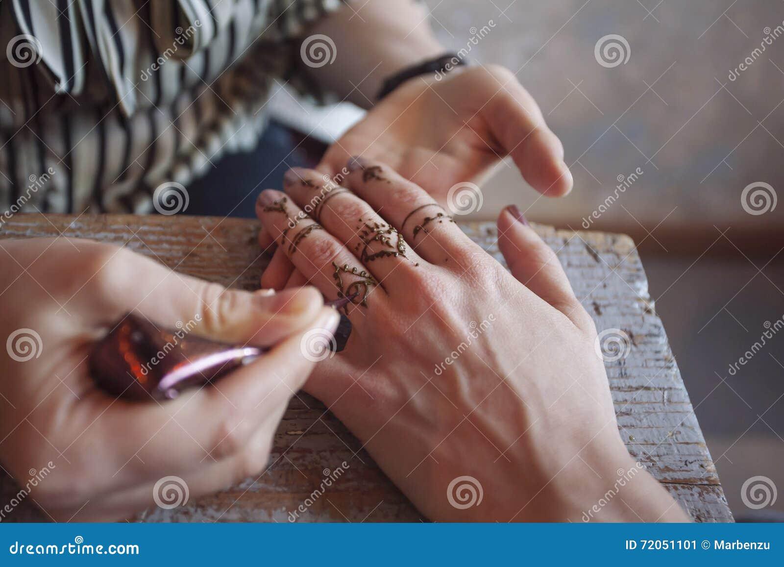 Artiste appliquant le tatouage de henné sur des mains de femmes