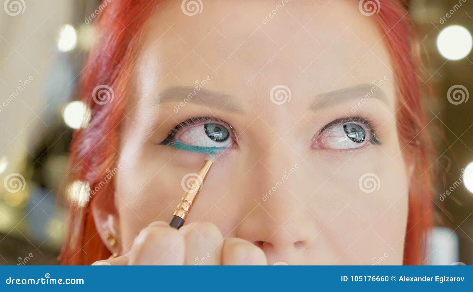 Artiste de maquillage s appliquant le maquillage à l oeil modèle du ` s Fermez-vous vers le haut de la vue